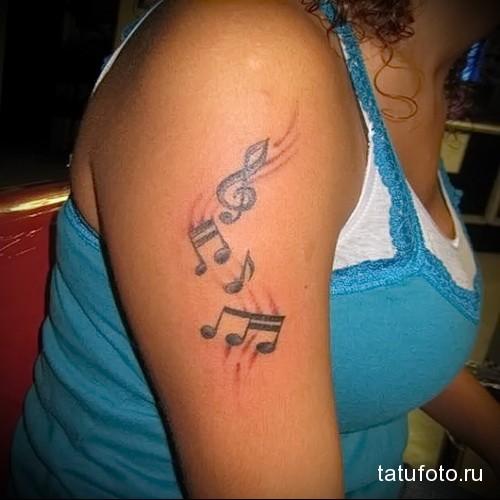 музыкальная татуировка на плече девушки