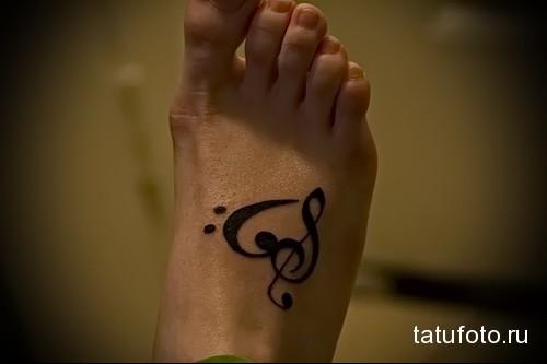 музыкальный рисунок - татуировка в нижней части ноги девушки