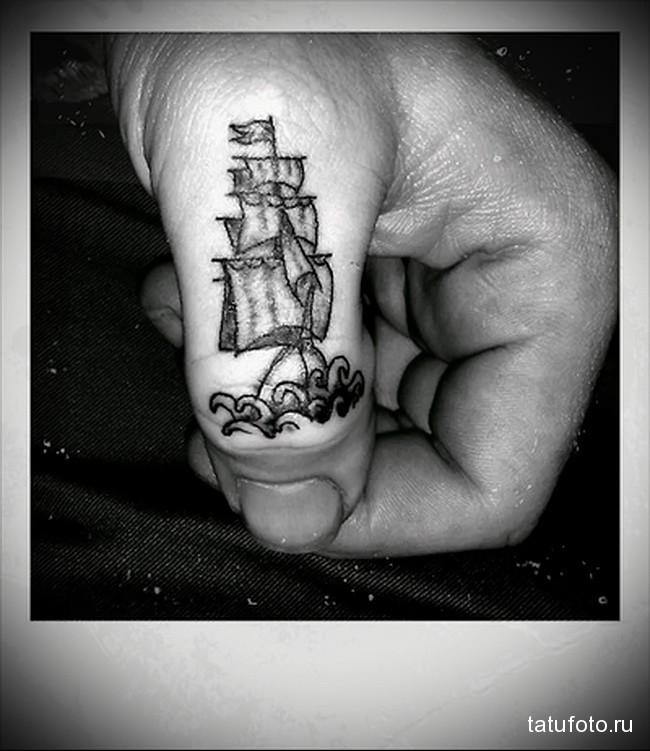 парусник на волнах в татуировке на пальцах для мужчины