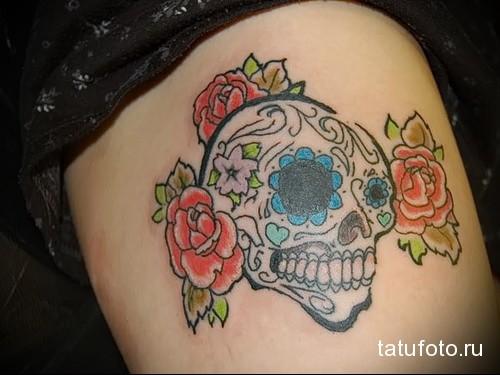 смешной череп с цветочками в татуировке на ногу для девушки