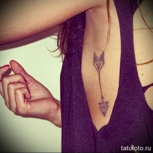 стрела направленная вниз - женская татуировка на боку