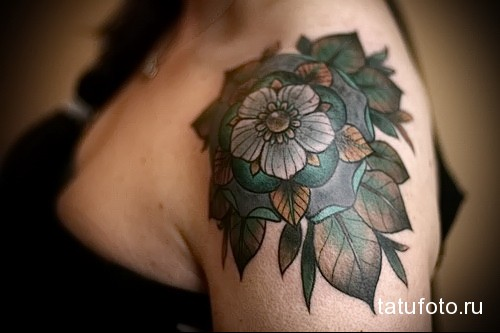 татуировка мандала из цветов и листьев на плече девушки