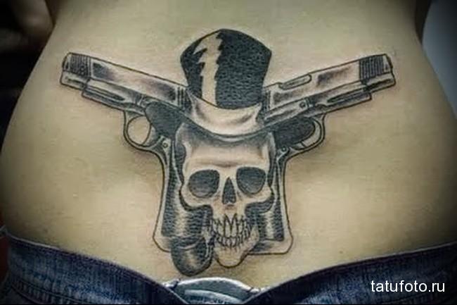 тату череп с трубкой в котелке и пистолеты - татуировка на пояснице женская фото