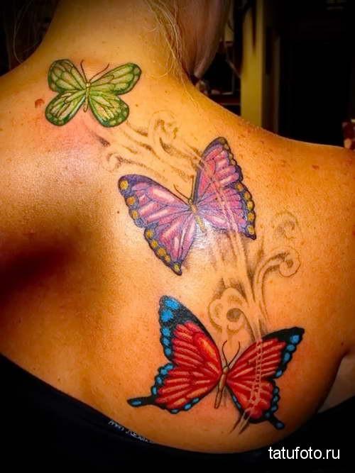 три цветные бабочки в полете тату на спине женская