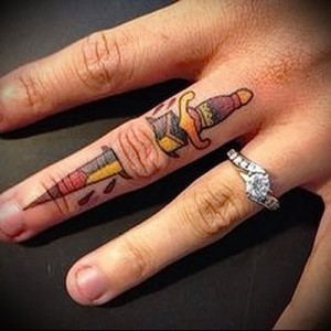 dagger tattoo on his arm