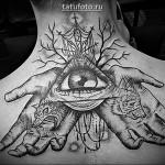 Татуировка глаз в треугольнике на спине девушки