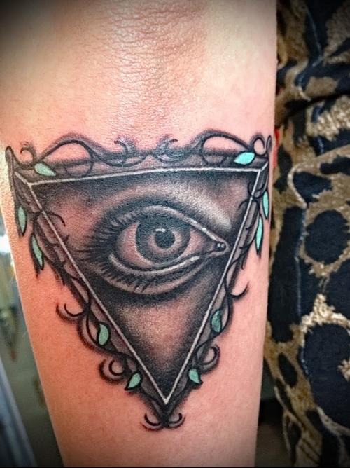 Всевидящее око тату в треугольнике на женской руке
