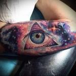 Всевидящее око и космос - цветная татуировка на руке