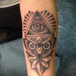 Татуировка всевидящее око и сова на плече мужчины