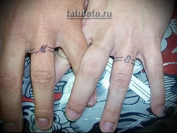 парная татуировка колечки с инициалами партнера