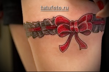 татуировка подвязка для чулков и красный бант на ноге