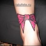 тату розовый бант в горошек на ноге