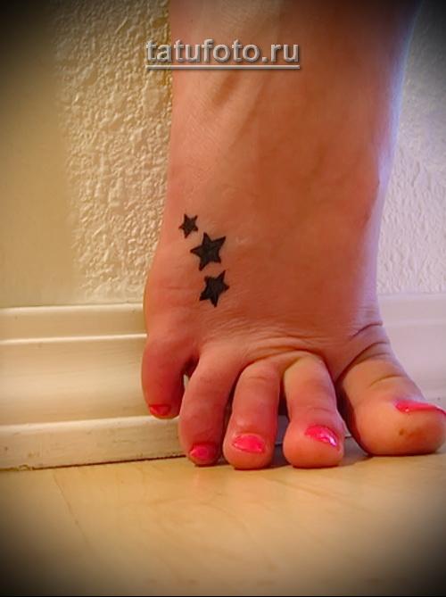 три маленькие звездочки в элегантной татуировке на женской ноге