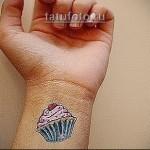цветная татуировка с пироженым на руке