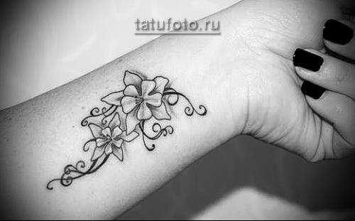 цветочки в татуировке для девушки на запястье