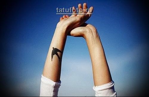 черная ласточка тату на руку женщине