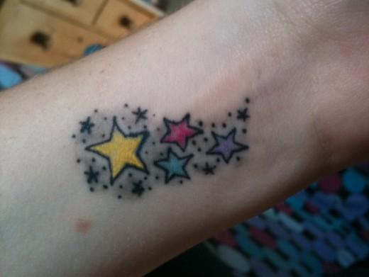 татуировка маленькие цветные звезды на запястье