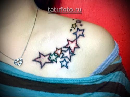 татуировка много цветных звездочек на ключице девушки