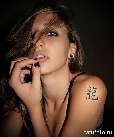 девушка с татуировкой иероглиф на левом плече