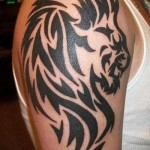 трайбл тату - лев на плече мужчины