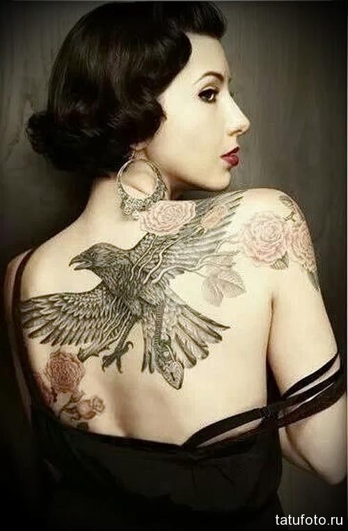 тату ворон и розы на спине девушки