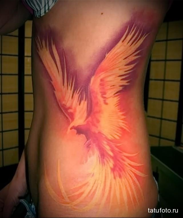 жар птица тату на боку девушки - яркий рисунок