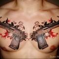 два больших пистолета в тату на груди