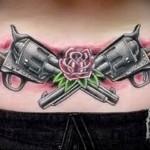 татуировка дле девушки с пистолетами и цветами на пояснице