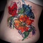 тату с разноцветными цветами и бабочкой на боку