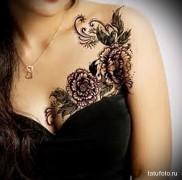 черные цветы в тату на груди и плече