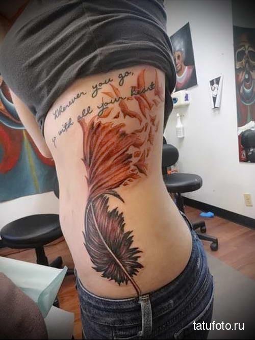 большое перо и надписи на боку у девушки - готовая татуировка на фото