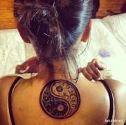 красивая татуировка с символом инь янь на спину девушке