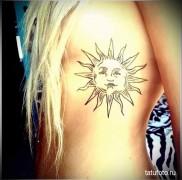 татуировка солнце у красивой блондинки на боку