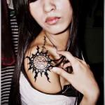 татуировка солнце черным цветом на плече у симпатичной азиатской девушки