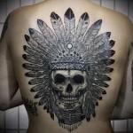 татуировка череп в головном уборе из перьев на спине - индейская татуировка