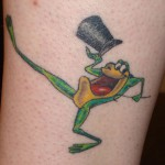 Тату лягушка в танце с котелком и тростью