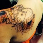 Тату слона индийского и цветы на левой лопатке девушки