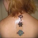 тату два иероглифа и цветной цветок на шее девушки сзади