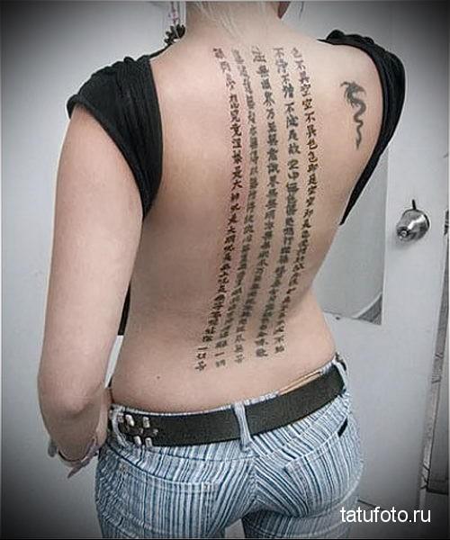 Тату на спине девушки - пять столбиков с иероглифами