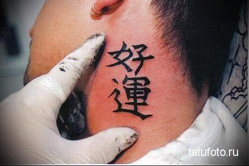 Тату иероглифы на шее возле уха у мужчины