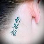 Тату три небольших иероглифа за ухом у девушки