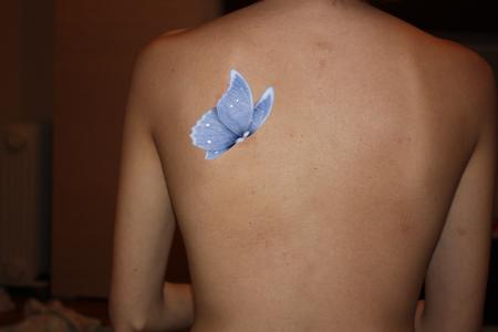 тату голубая бабочка на левой лопатке у девушки