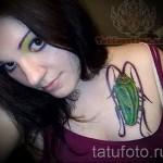 Тату насекомые - зеленый таракан на груди у девушки