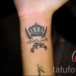 тату корона на запястье с иероглифами и скрещенными мечами