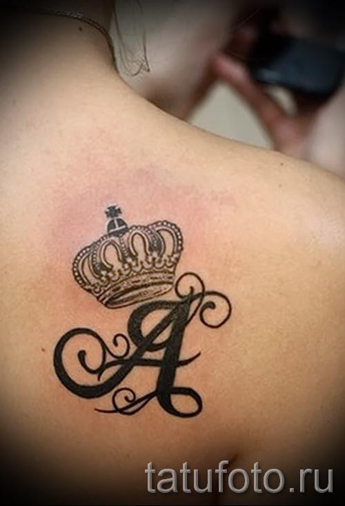 тату корона на спине - женская с красивой прописной буквой А