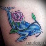Тату дельфин который несет цветок во рту