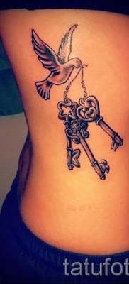 Тату замок и ключ фото пример – с птичкой – выполнена на боку у девушки