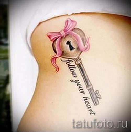 Тату ключ с бантиком и надпись на ребрах девушки