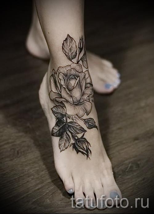 Тату черная роза внизу ноги у девушки