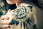 Тату черная роза на лопатке и плече у девушки